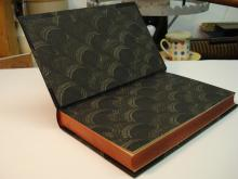Dance of Death, bound in half leather, black morocco with paste paper sides and end papers.